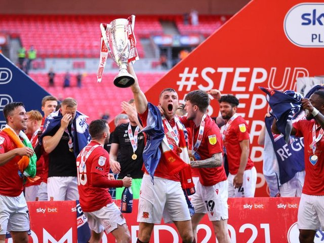 Morecambe skipper Sam Lavelle lifts the League Two play-off final winners' trophy