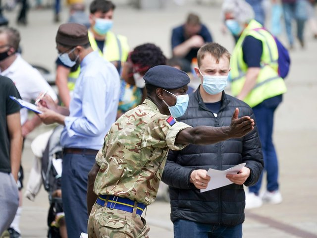 Soldiers from the Royal Horse Artillery guide members of the public at a rapid vaccination centre, set up outside Bolton Town Hall on June 09, 2021.