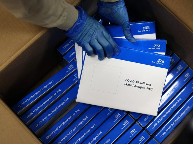 A health worker removes Covid-19 test kits from a box at a NHS Test and Trace Covid-19 testing unit.  (Photo by ADRIAN DENNIS / AFP) (Photo by ADRIAN DENNIS/AFP via Getty Images)