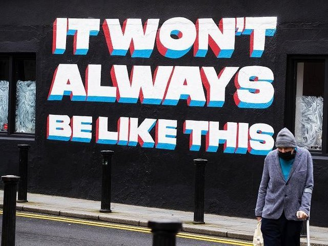 A man walks past a mural by Emmalene Blake in Dublin's city centre quoting a song title by Irish rock band 'Inhaler'