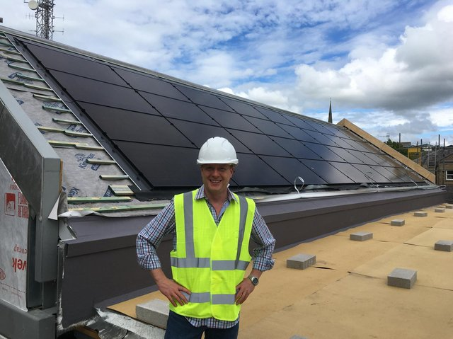 Vicar Jon Scamman by the solar panal roofing on the new St Thomas church centre.